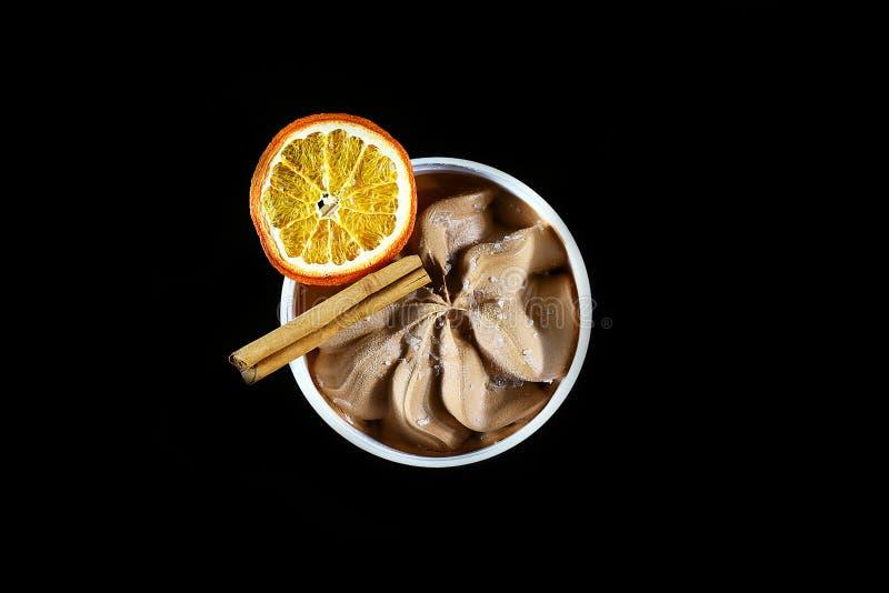 Zakończenie czekoladowy lody, kij cynamon i plasterek odizolowywający na czarnym tle wysuszona pomarańcze, odgórny widok z przest zdjęcie royalty free