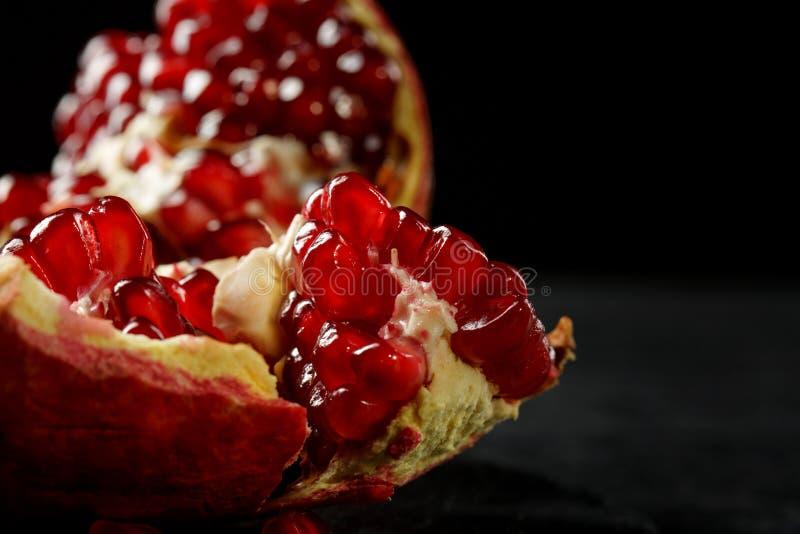 Zakończenie czerwony garnet Słodkogórzki granatowiec na czarnym tle Granatowiec pełno soczysty, fres zdjęcie stock