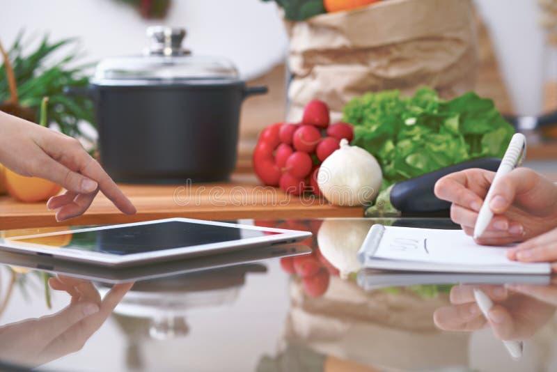 Zakończenie cztery ludzkiej ręki jest gestykuluje nad pastylką w kuchni Przyjaciele ma zabawę podczas gdy wybierający menu lub zdjęcia royalty free