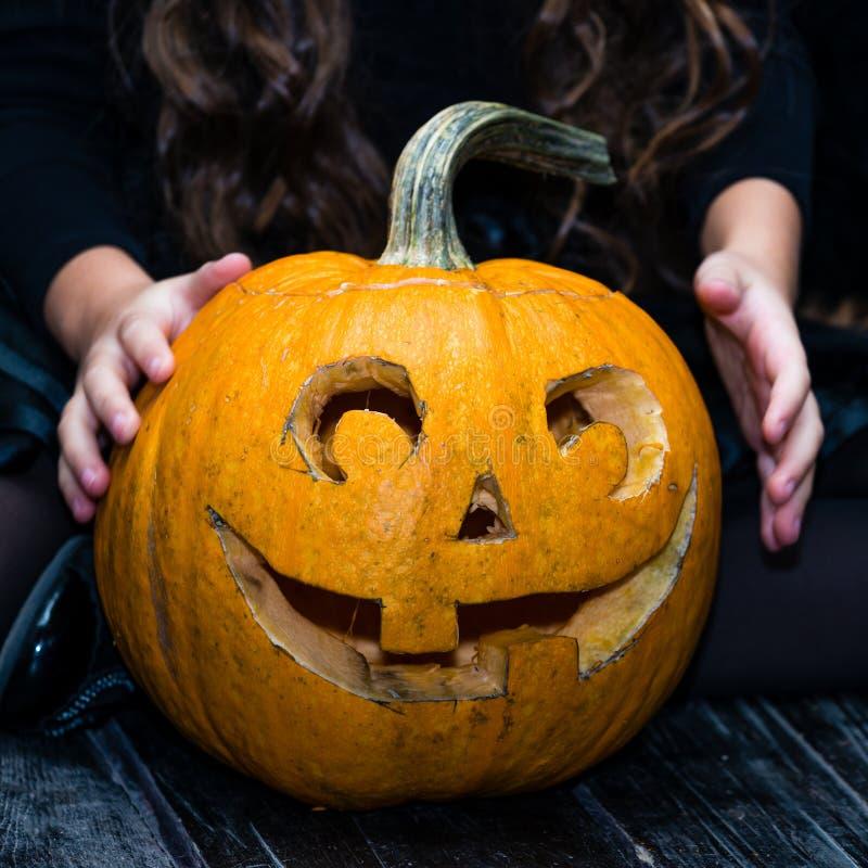 Zakończenie dziewczyny obsiadanie blisko Halloweenowego bani głowy dźwigarki lante fotografia royalty free