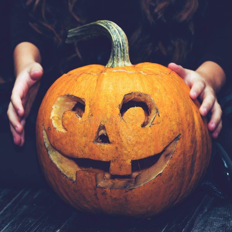 Zakończenie dziewczyny obsiadanie blisko Halloweenowego bani głowy dźwigarki lante obraz stock
