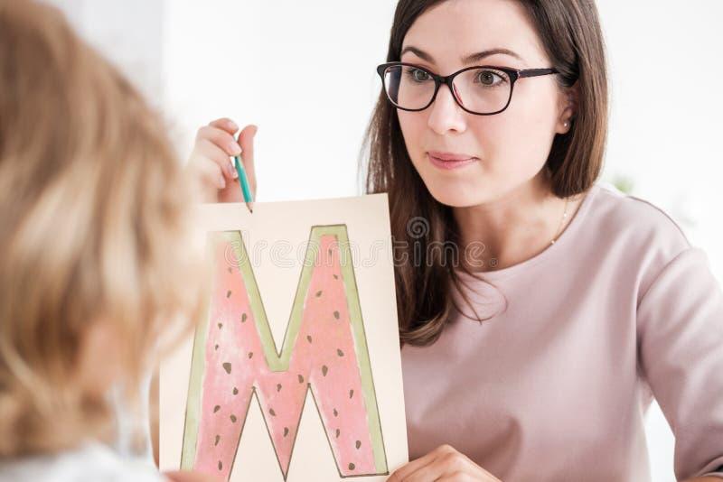 Zakończenie fachowy rozwoju dziecka terapeuta pokazuje podpierającego obrazek listowy ` m ` dzieciak podczas spotkania zdjęcia stock