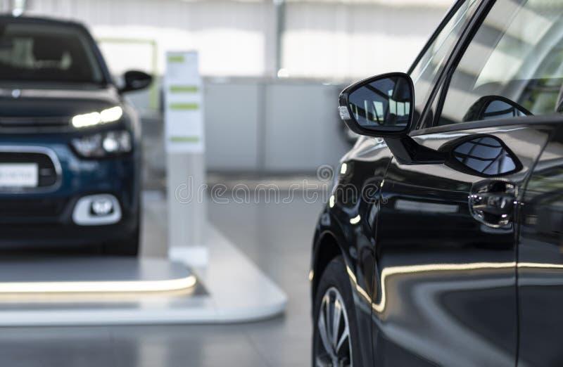 Zakończenie fotografia błyszczący samochód i inny jeden w zamazanej tło pozyci w jaskrawym samochodowego wynajem wnętrzu fotografia royalty free