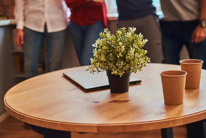 Zakończenie fotografia laptop, dwa papierowej filiżanki i kwiat na stole w studenckim dormitorium, fotografia stock