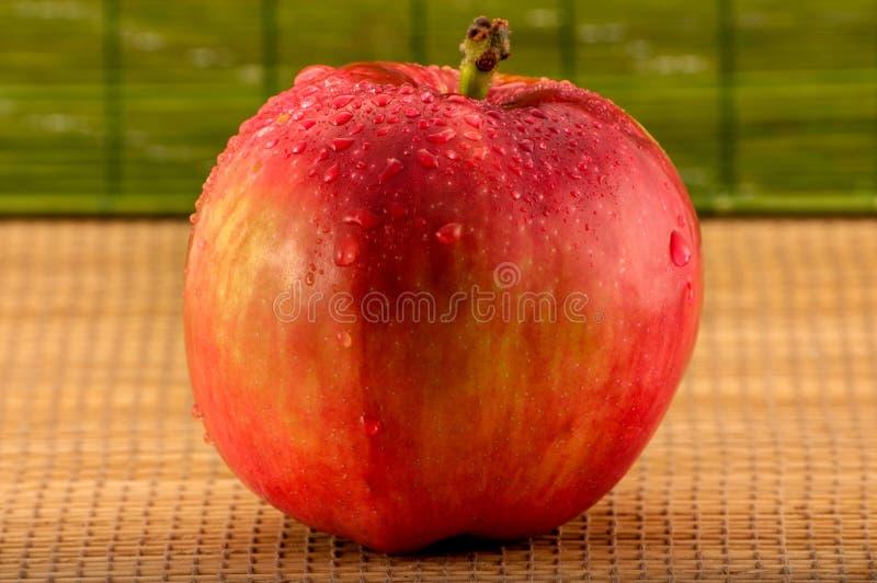 Zakończenie fotografia mokry czerwony jabłko z wodą opuszcza na zamazanym bambusowym tle obrazy stock