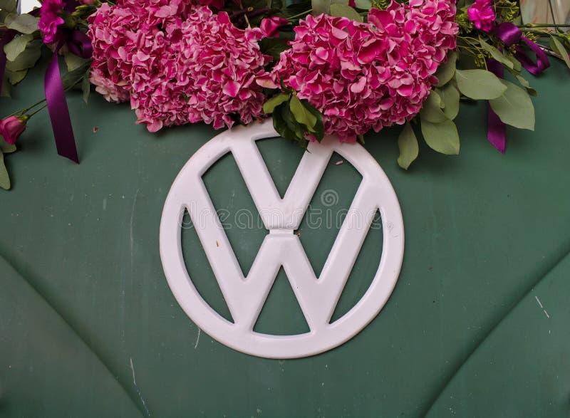 Zakończenie fotografia przód zieleni VW T3 samochód dostawczy z białym VW logem dekorującym z menchiami kwitnie Bremen Niemcy, Li fotografia stock