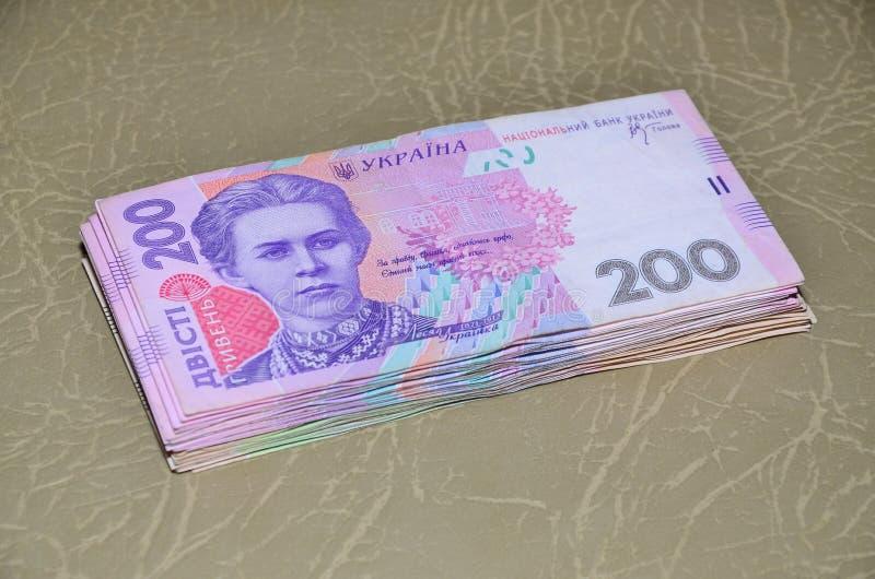 Zakończenie fotografia set Ukraiński pieniądze z wartością nominalną 200 hryvnia, kłama na brown skóry powierzchni Tło zdjęcie royalty free
