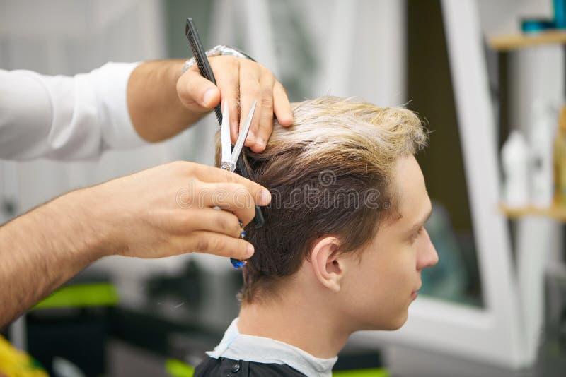 Zakończenie fryzjera męskiego ` s up wręcza robić nowemu ostrzyżeniu dla młodego klienta obrazy royalty free
