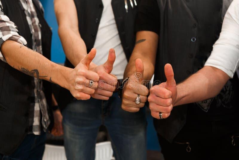 Zakończenie fryzjery męscy pokazuje kciukowi up gest zdjęcie stock