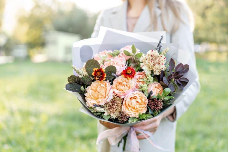 Zakończenie jesieni piękny bukiet w rękach kwiatu przygotowania z różnorodnymi kwiatami zielony gazon na tle jaskrawy fotografia stock