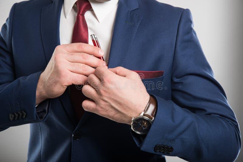 Zakończenie jest ubranym kostiumu kładzenia pióro w kieszeni biznesowy mężczyzna obrazy stock