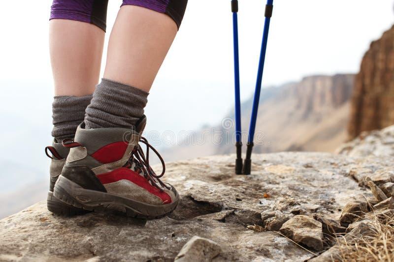 Zakończenie kobieta iść na piechotę w trekking butach z kijami dla Północnego odprowadzenia przeciw tłu skały i odległy obrazy royalty free