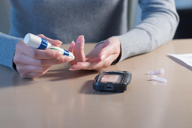 Zakończenie kobieta wręcza używać lancet na palcu czek krew obraz stock