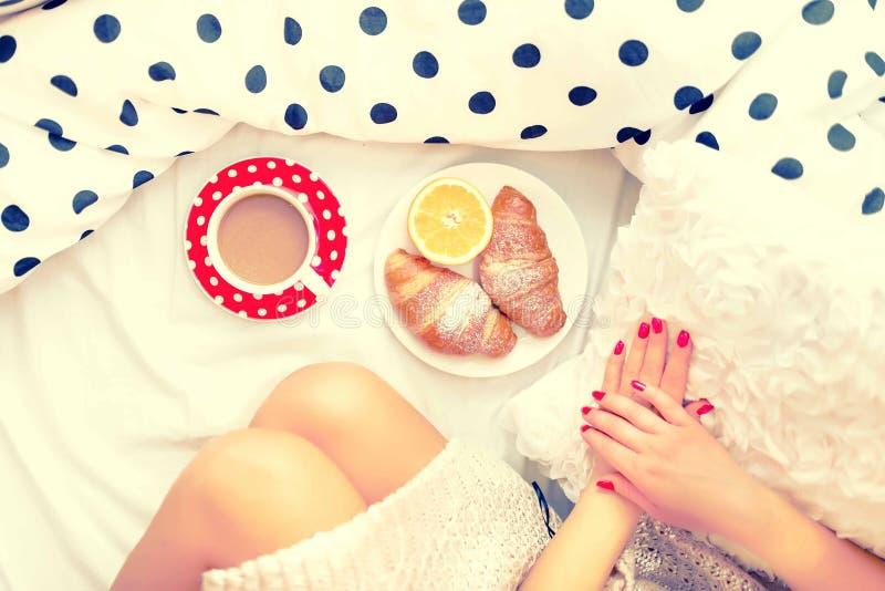 Zakończenie kobiety śniadanie w łóżku z i nogi croissants, kawą i sokiem pomarańczowym, obrazy stock