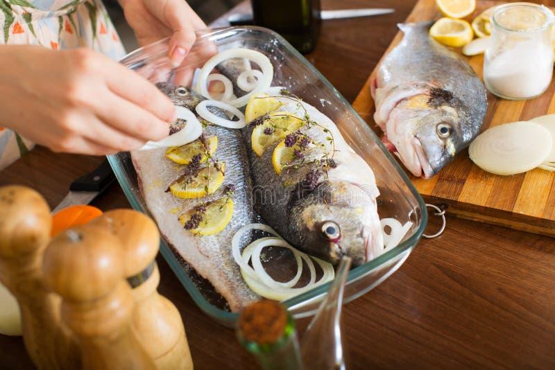 Zakończenie kobiety kucharstwa ryba fotografia stock