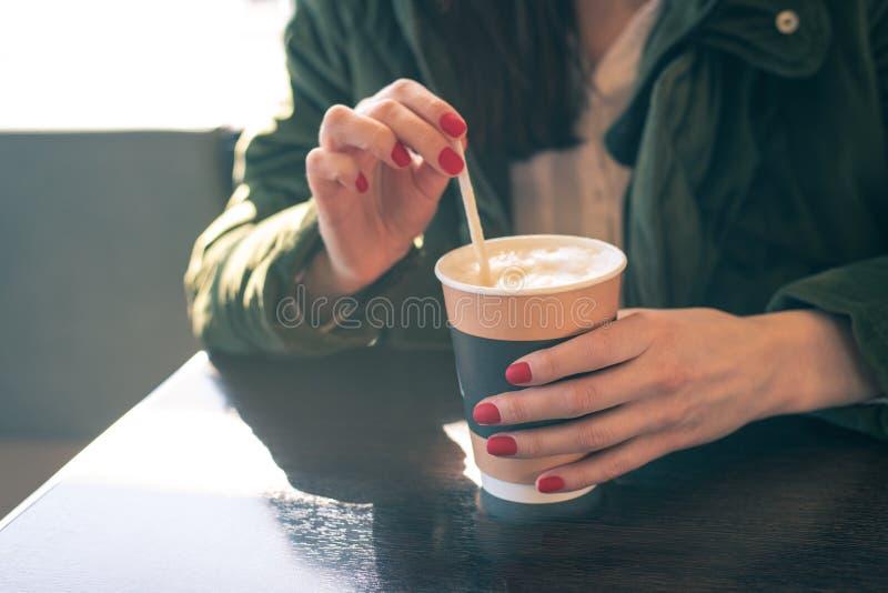 Zakończenie kobiety ` s ręki z filiżanką kawy przy stołem w kawiarni cukrowy mieszać, rozpuszczenie obraz royalty free