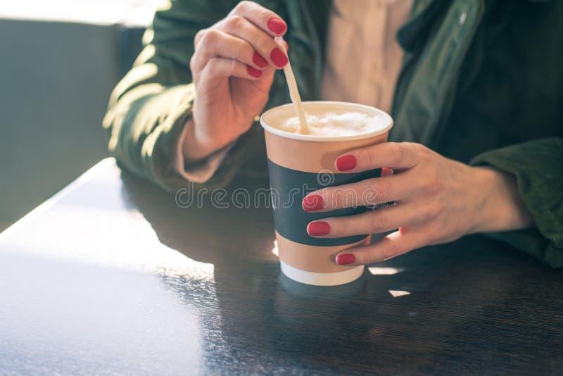 Zakończenie kobiety ` s ręki z filiżanką kawy przy stołem w kawiarni cukrowy mieszać, rozpuszczenie zdjęcia stock