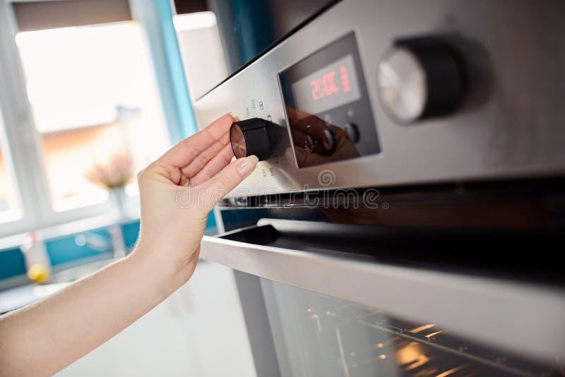 Zakończenie kobiety up wręcza położeniu kulinarnego tryb na piekarniku zdjęcie royalty free