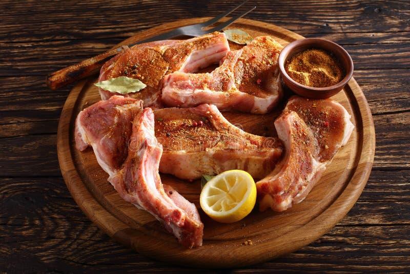 Zakończenie korzenni uncooked wieprzowina kotleciki fotografia royalty free