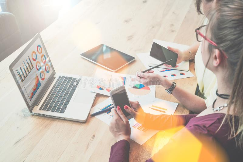 Zakończenie laptop z wykresami, diagramy na ekranie, smartphones w rękach młodzi bizneswomany zdjęcia royalty free
