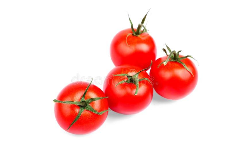 Zakończenie lata żniwo jaskrawi czerwoni pomidory z zielenią opuszcza na białym tle Soczyści, dojrzali i świezi pomidory, zdjęcia stock