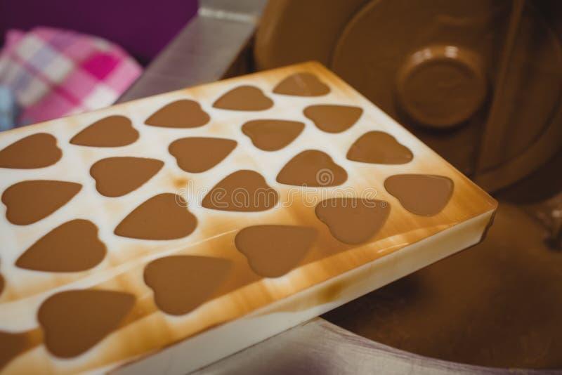 Zakończenie lejnia wypełniał z rozciekłą czekoladą na kontaminaci maszynie obrazy stock