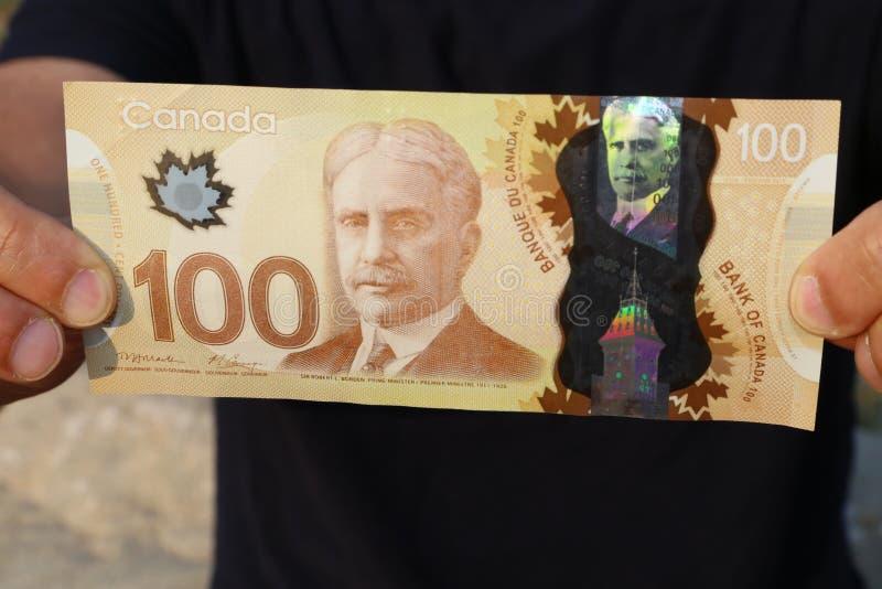 Zakończenie mężczyzna ` s up wręcza mieniu Kanadyjskiego pieniądze $100 rachunek zdjęcia stock