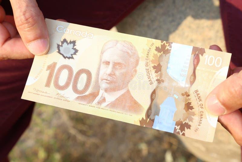 Zakończenie mężczyzna ` s up wręcza mieniu Kanadyjskiego pieniądze $100 rachunek zdjęcie royalty free