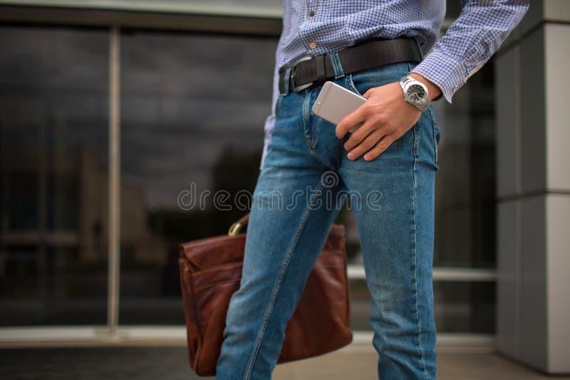 Zakończenie mężczyzna z nowym telefonem i teczką na miastowym tle Biznesowa oferta pracy przeciw pojęcie błękitny barwionej sieci obrazy stock