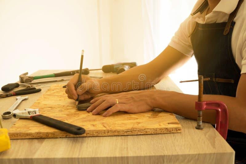 Zakończenie męski cieśla wręcza rysunek ocenę na drewnianej podłoga obraz royalty free