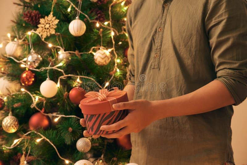 Zakończenie młody azjatykci mężczyzna trzyma boże narodzenie prezenta czerwonego pudełko na kanapy i choinki tle w domu obrazy stock