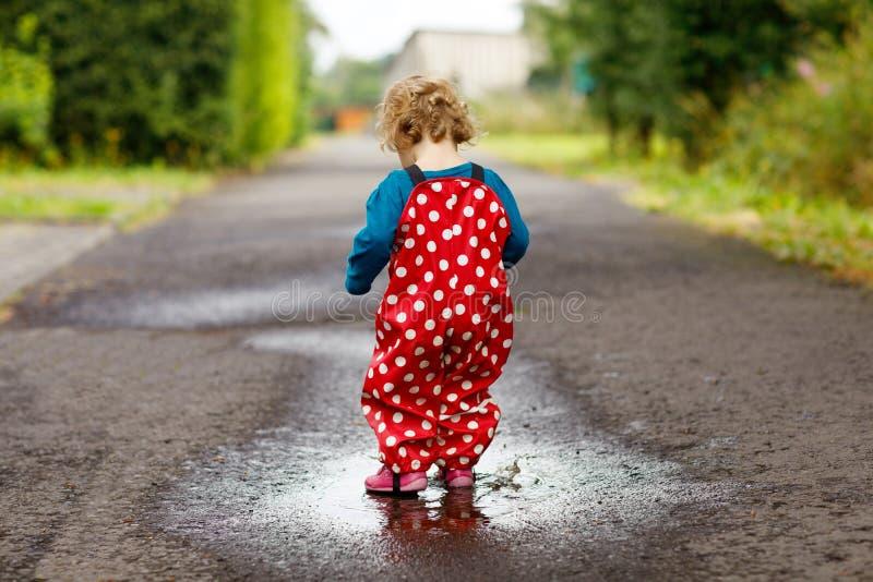 Zakończenie mała berbeć dziewczyna jest ubranym podczas sleet i odprowadzenie podeszczowych buty i spodnia, deszcz na zimnym dniu obrazy stock