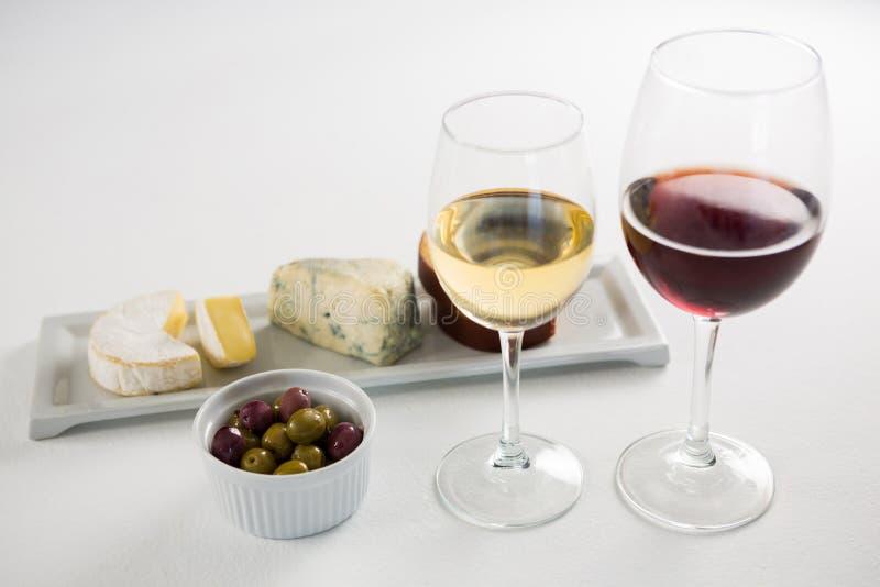 Zakończenie marynował oliwki z szkłami wino i ser w tacy zdjęcie royalty free