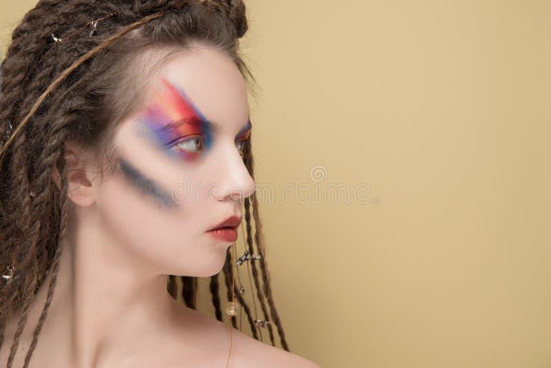 zakończenie mody kobiety model z kolorową abstrakcjonistyczną makeup i dreadlocks fryzurą zdjęcie stock