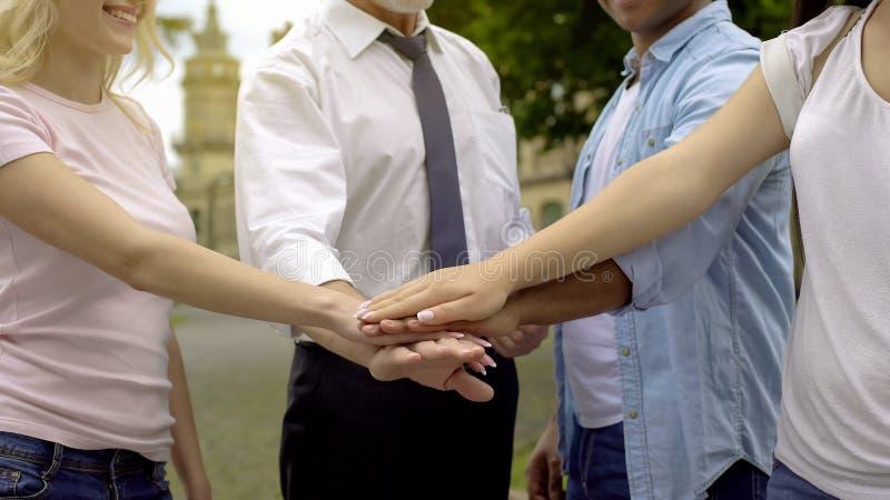 Zakończenie nauczyciel i ucznie stawia ręki na stosie wpólnie, współpraca zdjęcie royalty free