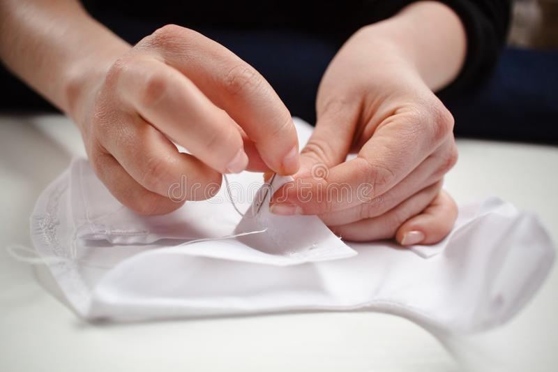 Zakończenie obrazek ręki szwaczka przy pracą z białą tkaniną obraz stock