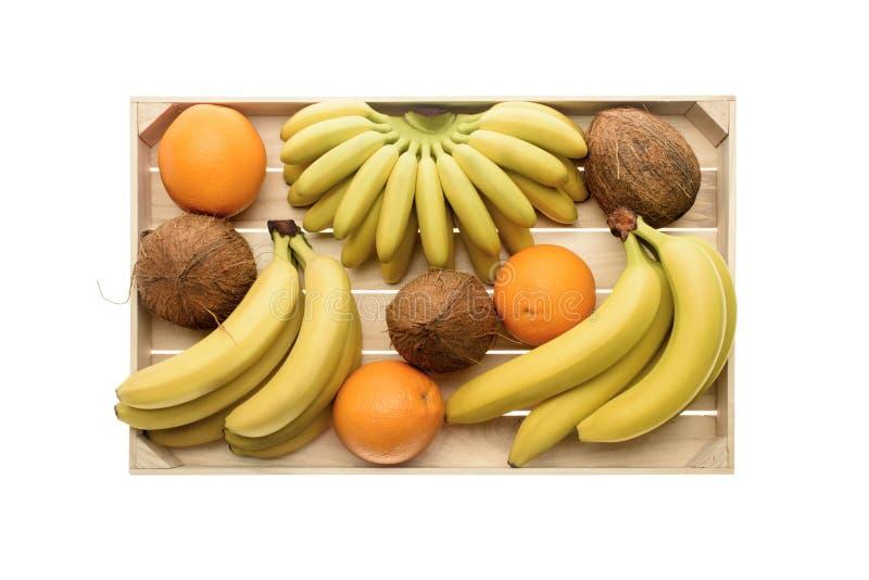 zakończenie odgórny widok świezi dojrzali banany, koks i pomarańcze w drewnianym pudełku, zdjęcia stock
