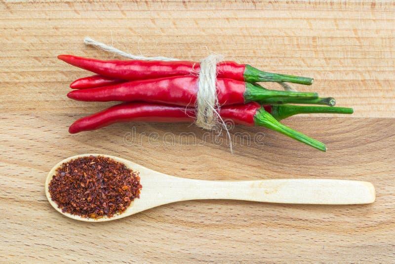 Zakończenie odgórny widok czerwony chili pieprz, wiązany z warkoczem i łyżką na drewnianym tle obraz stock