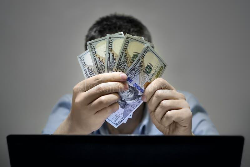 Zakończenie online używa laptop ręki robi zakupy podczas gdy trzymający USA dolary obraz stock
