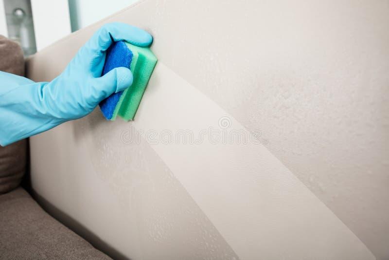 Zakończenie osoby ` s ręki Cleaning poduszki kanapy meble zdjęcia stock