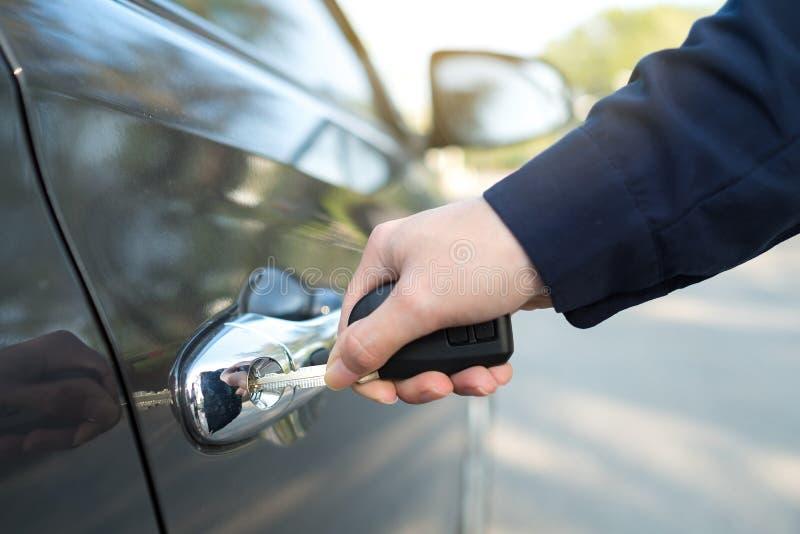 Zakończenie otwiera samochodowego drzwi kluczem ręka zdjęcia royalty free
