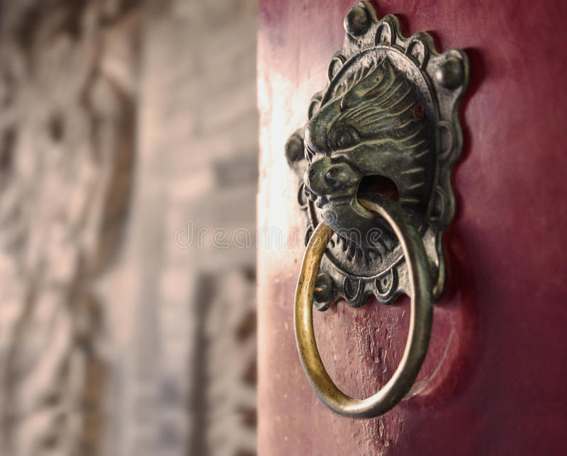 Zakończenie ozdobny złocisty drzwiowy knocker na czerwonym drzwi zdjęcia stock
