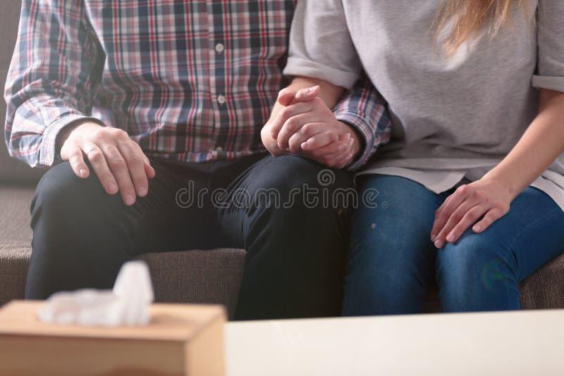 Zakończenie pary mienia ręki podczas gdy siedzący na leżanki duri fotografia stock