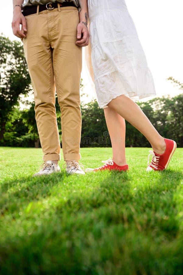 Zakończenie pary ` s up iść na piechotę w keds na trawie obrazy stock
