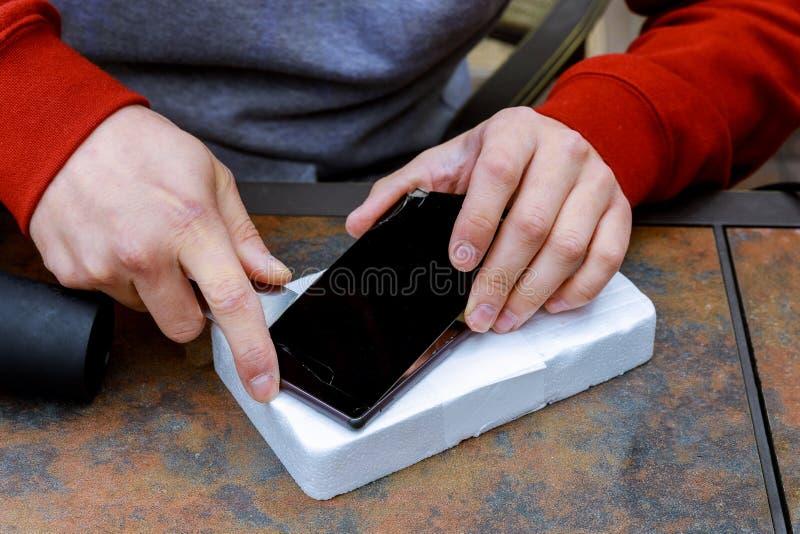Zakończenie Person& x27; s ręki naprawianie Uszkadzający ekran Na telefonie komórkowym obrazy stock