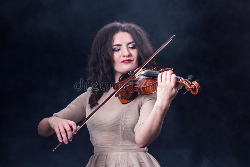 Zakończenie Piękna dziewczyna z ciemnym włosy na dymiącym tle Skrzypce i łęk w żeńskich muzykalnych rękach piękna dziewczyna obrazy royalty free