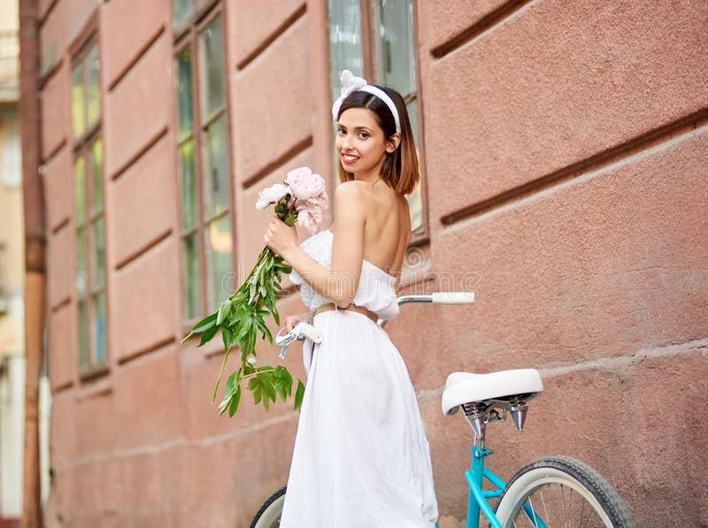 Zakończenie piękna kobieta z peoniami w rękach zbliża retro bicykl zdjęcie royalty free