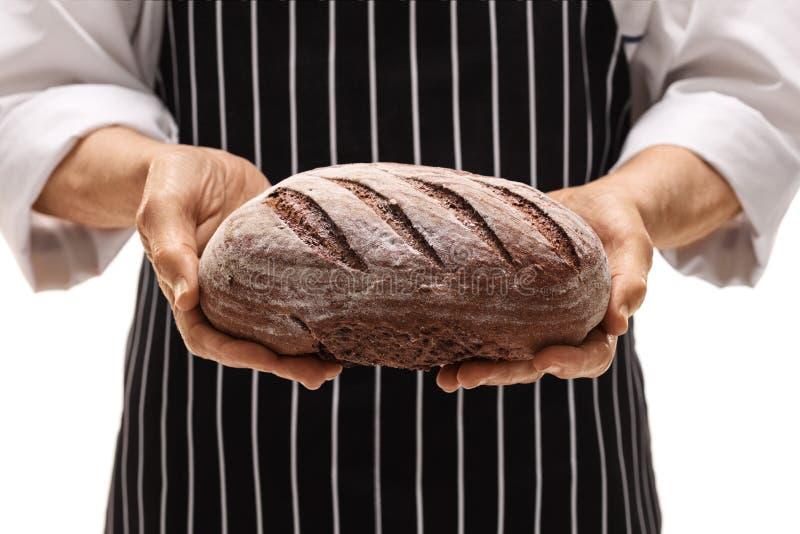 Zakończenie piekarz daje bochenkowi chleb zdjęcia stock