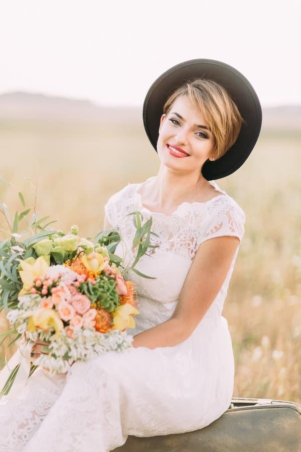 Zakończenie pionowo portret blondynki panna młoda trzyma dużego colourful bukiet w roczniku smokingowym i kapeluszu fotografia royalty free