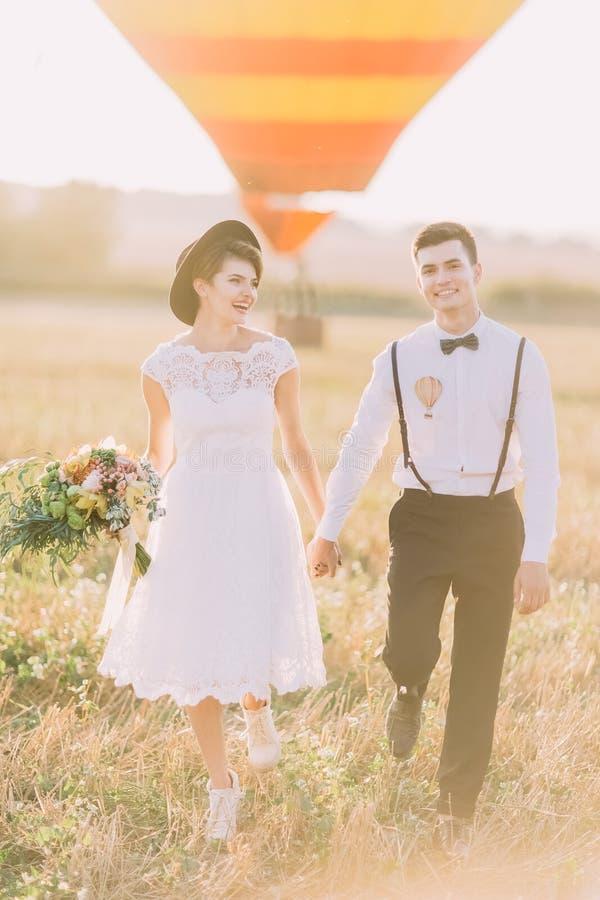 Zakończenie pionowo portret szczęśliwi nowożeńcy trzyma ręki i odprowadzenie w polu podczas zmierzchu _ fotografia royalty free
